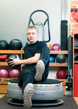 Fitness-Übung mit Ball auf Power Plate